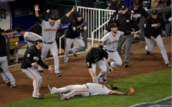 Third baseman Pablo Sandoval hits the ground after catching a foul pop fly for the last out of the 2014 World Series, as the Giants erupt from their dugout.