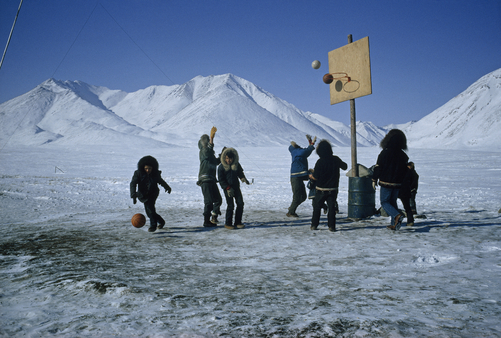 Eskimos play basketball on a court of ice near snow covered mountains.